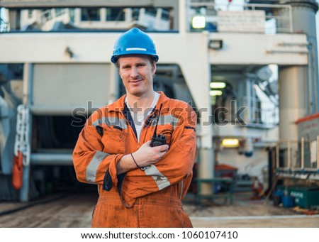 Marine Deck Officer or Chief mate on deck of offshore vessel or ship , wearing PPE personal protective equipment - helmet, coverall. He speaks to VHF walkie-talkie radio