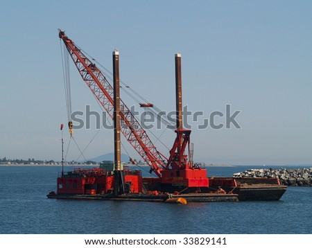 Marine dredge and pile driver sits anchored off of the Taawasan Ferry Terminal near Vancouver, BC.  Point Roberts, Washington can be seen in the background