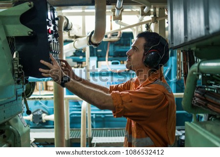 Marine engineer inspecting ship's engine in engine control room ECR. Seamen's work.