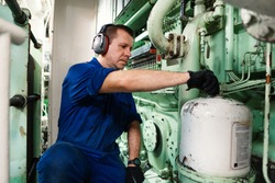 Marine engineer officer controlling vessel engines and propulsion in engine control room ECR. Ship onboard maintenance