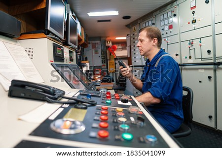 Marine engineer officer controlling vessel engines and propulsion in engine control room ECR. Ship maintenance Start or stop of main engine