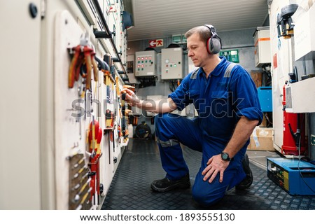 Marine engineer officer in engine control room ECR. He works in workshop and chooses correct tools and equipment Imagine de stoc ©