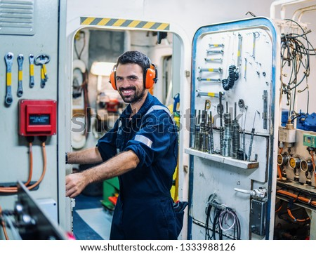 Marine engineer officer in engine control room ECR. Seamen's work. He starts or stops main engine of ship #1333988126