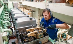 Marine engineer officer reparing vessel engines and propulsion in engine control room ECR. Ship onboard maintenance
