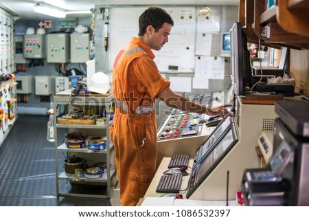 Marine engineer officer starts or stops main engine of ship in engine control room ECR. Seamen's work.