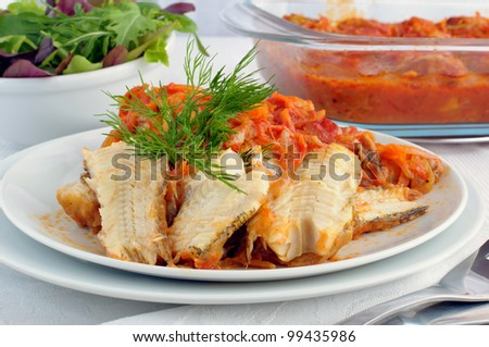 Marine fish baked with onions and carrots in tomato sauce