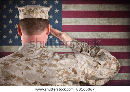 Marine in Desert Fatigues Saluting an American Flag - stock photo