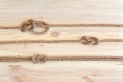 Marine knots used in yachting: figure eight knot, square knot, bowline knot. Nautical knots on wooden background.