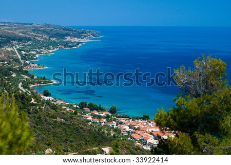 Marine landscape. Greece, Kassandra, Chalkidiki. Blue sea and sky, small town with red roofs.