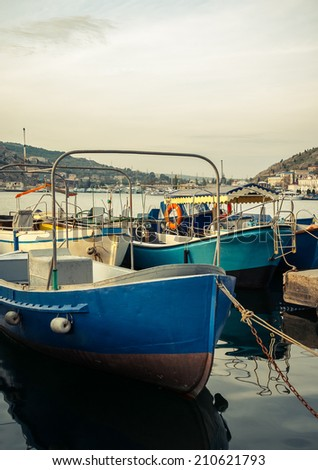 Marine landscape with a boats in harbor. Old boats on pier - fisherman\'s transport. Bow of the fishing boat with reflection on sea surface. Blue motorboats are moored in harbor.