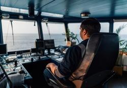 Marine navigational officer during navigational watch on Bridge . Work at sea