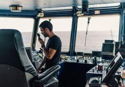 Marine navigational officer is reporting by VHF radio during navigation watch. Bridge GMDSS watch