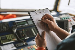 Marine navigational officer or chief mate on navigation watch on ship or vessel. He fills up checklist. Ship routine paperwork