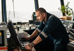 Marine navigational officer or chief mate on navigation watch on ship or vessel. He is sets up radar for collision prevention