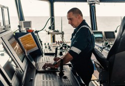 Marine navigational officer or technician is using laptop or notebook at sea. Job at sea