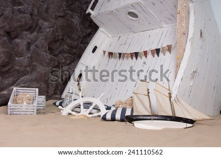 Marine or nautical themed still life depicting a ship wreck with a wooden boat upended in the sand with a ships wheel, lantern, capsized toy yacht and wooden crates scattered around