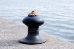 Marine ship mooring bollard on a dock by the waters edge