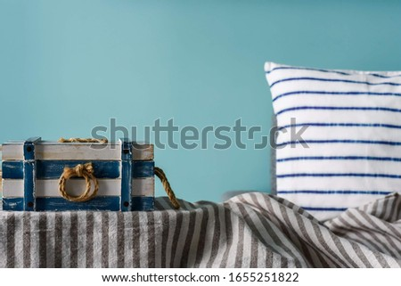 Marine style in the interior of the apartment - a sofa with pillows and the striped casket. Blue room marine concept