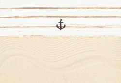 Marine summer background of white wooden boards on a sand with decorative anchor.