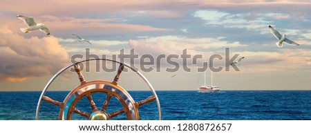 Marine sunrise with a skippers wheel and sailing yacht on skyline. Calm landscape with a cloudy sky and seagulls over the sea for your concept about romantic sea voyage on a ship around the world.