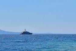Marine yacht on the border of turquoise sea and blue sky on sunny day