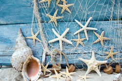 Maritime souvenir from holidays on the beach: Seashell background border on rustic blue wood. View on different starships and seashells with white sand and fishnet.
