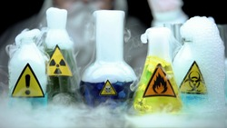 Marked dangerous liquids evaporating in flasks in front laboratory worker