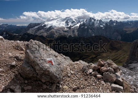 Marked rock in front of a wide view over Mt. Marmolada