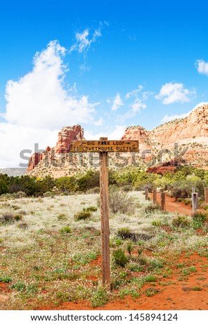 Marker for Big Park Loop and Courthouse Butte hiking trail in Sedona, Arizona with red rock mountains and a bright blue sky in the background.