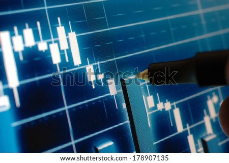 Marker pointing at the stock chart on monitor
