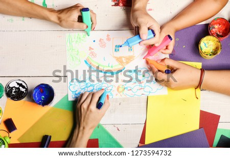 Markers in male and female hands draw on white paper. Hands hold colorful markers and draw kids illustration, top view. Artists wooden table with paints and colored paper. Art and idea concept #1273594732
