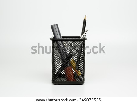 Markers, pen, pencil in black basket isolated on white background