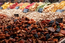 Market counter with various assorted dried fruits and nuts. Healthy food. Local market.translation: compote