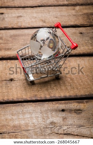 Market. Glass globe in the shopping trolley global market concept