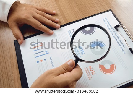 Market research. Businessman hand holding magnifier and closer study report from market research. Concept for website banner, background, presentation template and marketing materials.