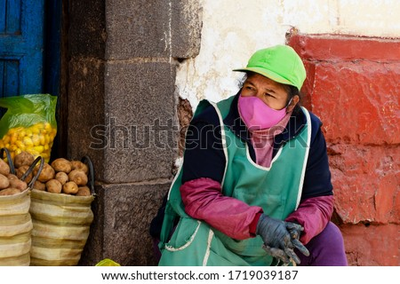 Market seller in respiratory mask during coronavirus pandemic in Cusco, Peru in Latin South America. Epidemic of coronavirus covid-19