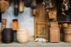 Market selling different baskets on side of the road sleeping dog