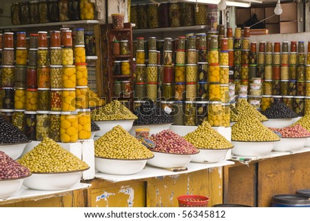 Market stall selling fresh olives and bottled food in the main souk of Marrakesh, Morocco.