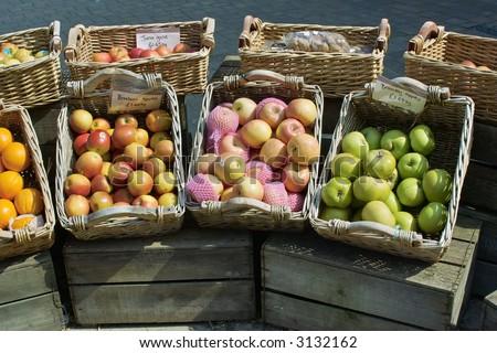 market stall selling fruit in baskets outside in open air
