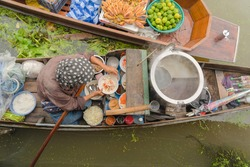 Market woman cooking noodle at Damnoen Saduak Floating Market or Amphawa. Local people sell fruits, traditional food on boats in canal, Ratchaburi District, Thailand. Famous Asian tourist attraction.