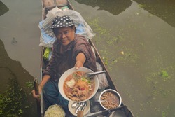 Market woman giving noodle at Damnoen Saduak Floating Market or Amphawa. Local people sell fruits, traditional food on boats in canal, Ratchaburi District, Thailand. Famous Asian tourist attraction.