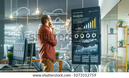 Marketer Looks at Interactive Touchscreen Whiteboard Showing Latest Graphs and Charts on Statistical Growth. He Works in the Creative Office. #1073312759