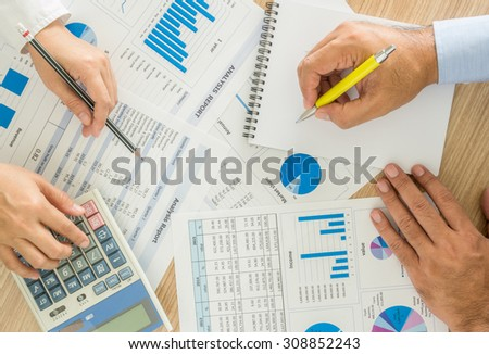 marketer worker analyzing statistical data on desk in office. top view