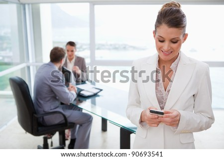 Marketing manager reading text message with her team sitting behind her - stock photo
