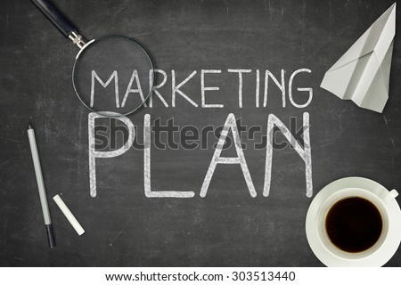 Marketing plan concept on black blackboard with coffee cupt and paper plane