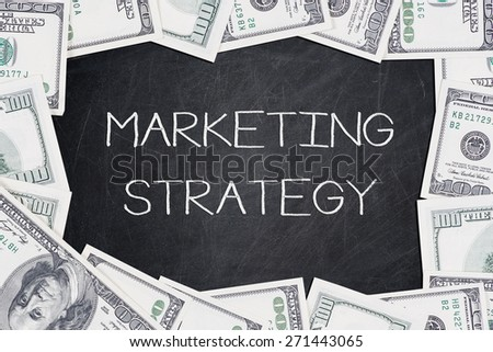 MARKETING STRATEGY text on a blackboard with border made of 100 US dollars.