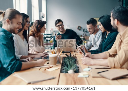 Marketing team. Group of young modern people in smart casual wear discussing something while working in the creative office