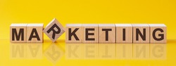 MARKETING word written on wood block. MARKETING text on table, concept. Word MARKETING is made of wooden building blocks lying on the table on a light yellow background.