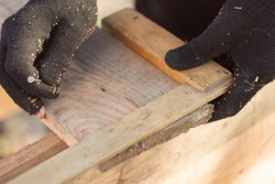 marking boards in black gloves with a wooden corner