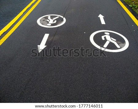 Photo of  Marking the footpath. Pedestrian path with directions. Sidewalk for pedestrians. Demarcation line. Permission to move people. Signs drawn on the pavement.